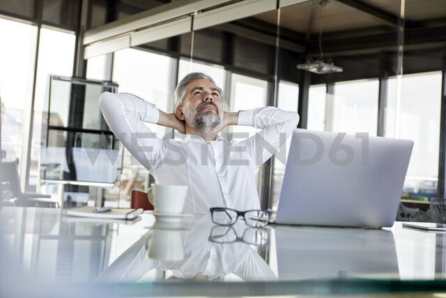 Businessman at desk in office leaning back - RBF06318
