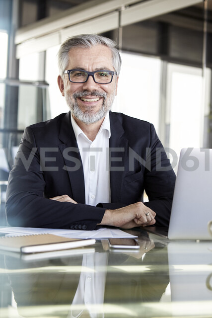 Portrait of smiling businessman at desk in office - RBF06327 - Rainer Berg/Westend61