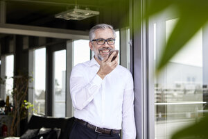 Smiling businessman standing at French door using cell phone - RBF06333