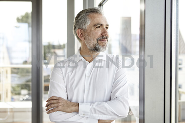 Portrait of smiling businessman looking out of window - RBF06336