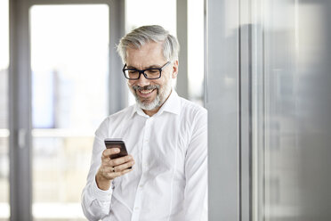 Smiling businessman at the window looking on cell phone - RBF06342