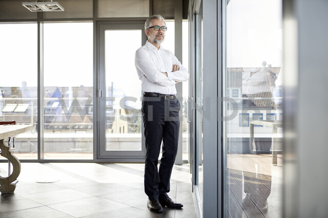 Businessman looking out of window - RBF06345