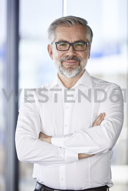 Portrait of smiling businessman standing at the window - RBF06351