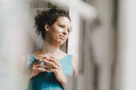 Pretty woman leaning on window, drinking coffee - KNSF04069