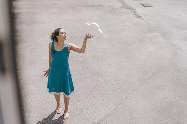 Woman standing in backyard, holding cloud symbol, blowing kiss - KNSF04075
