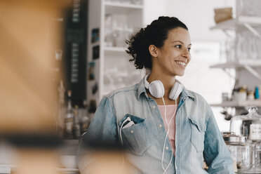 Young woman with headphones, working in coworking space - KNSF04087