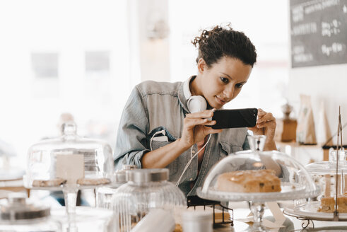 Woman taking pictures of cakes in coffee shop with her smartphone - KNSF04090