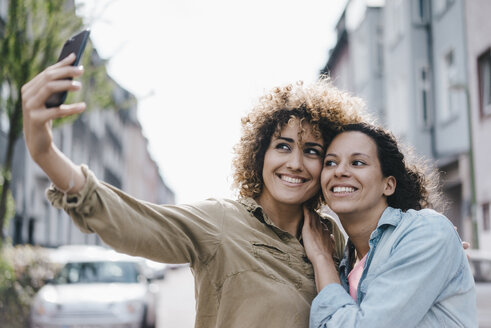 Best friends taking selfies with a smartphone in the city - KNSF04126