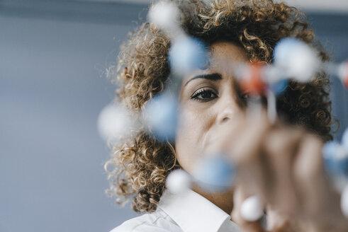 Female scientist looking at molecule model, looking for solutions - KNSF04156
