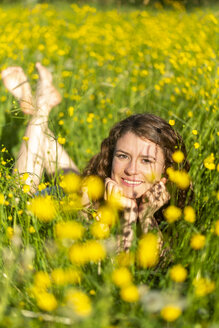 Young woman lying on flower meadow - SARF03804
