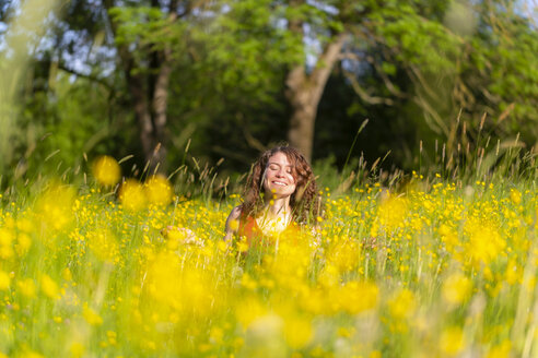 Young woman with closed eyes sitting on flower meadow - SARF03807