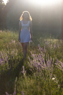 Young woman walking on flower meadow in the evening light - SARF03810
