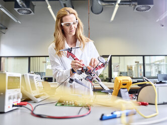 Female technician working in research laboratory, developing drone - CVF00882