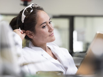 Female technician working in research laboratory in front of tablet - CVF00885