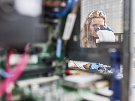 Female technician working with microscope in research laboratory - CVF00888