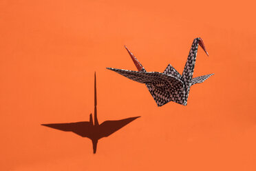 Origami crane, orange background, shadow, copy space - PSTF00137