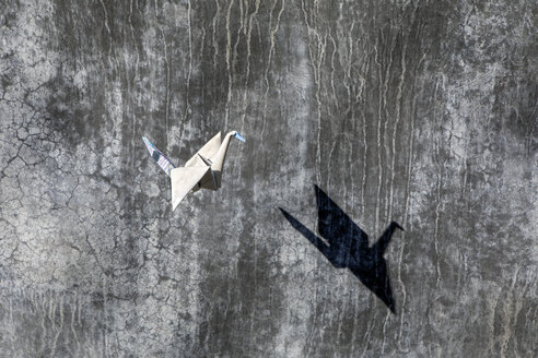 Origami crane flying, concrete wall - PSTF00140