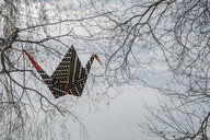 Origami crane in the air, twigs in background - PSTF00149