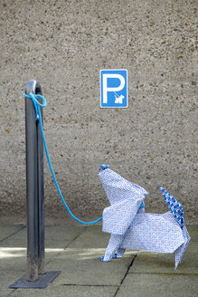 Origami dog in front of concrete wall, parking sign - PSTF00152