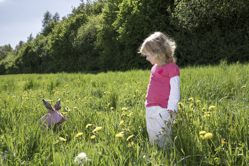 Little girl with origami rabbit on meadow - PSTF00167