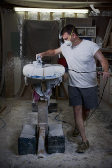 Mature man sanding a surfboard in his garage - CUF34518