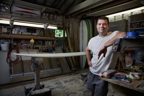 Portrait of mature man in his garage with surfboards - CUF34521