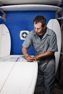 Mid adult man measuring surfboard in his workshop - CUF34524
