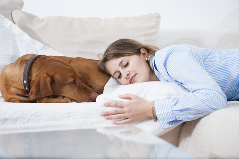 Young woman asleep with her dog on sofa - CUF34560