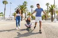 Carefree friends having fun with a skateboard on a promenade with palms - WPEF00450