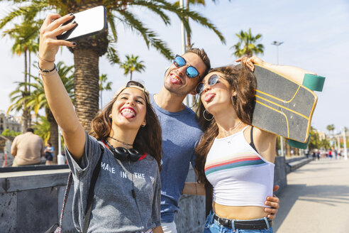 Three playful friends with skateboard taking a selfie - WPEF00456