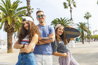 Three happy friends posing with skateboard on a promenade with palms - WPEF00465