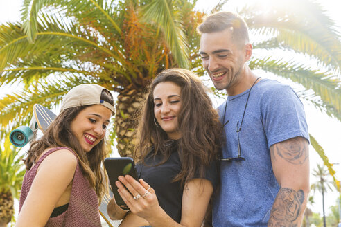 Friends sharing cell phone at a palm tree - WPEF00474