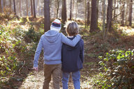 Twin brothers walking together in woods - CUF34633