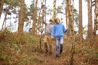 Twin brothers strolling in woods - CUF34651