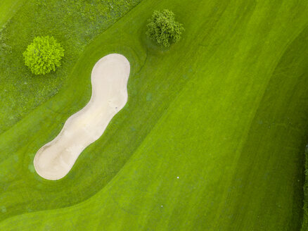 Germany, Baden-Wuerttemberg, Aerial view of golf course with bunker, green and hole - MMAF00399