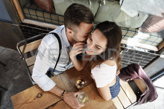 Affectionate couple having a drink at an outdoor bar in the city - JSMF00303