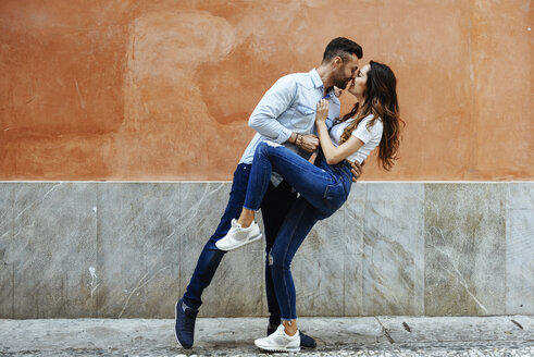 Affectionate couple in love kissing in front of a wall outdoors - JSMF00306