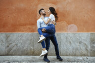 Carefree couple in love in front of a wall outdoors - JSMF00309