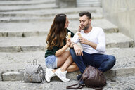 Tourist couple eating ice cream cones in the city - JSMF00321