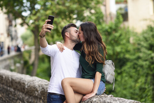 Couple in love in the city kissing and taking a selfie - JSMF00327