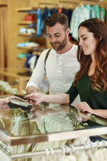 Couple in a boutique paying with smartphone - JSMF00336