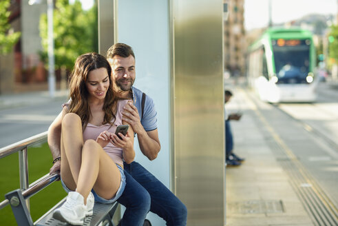 Couple looking at smartphone while waiting for tram at the station - JSMF00345