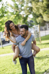 Happy man giving girlfriend a piggyback ride in park - JSMF00348