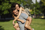 Happy man giving girlfriend a piggyback ride in park - JSMF00351