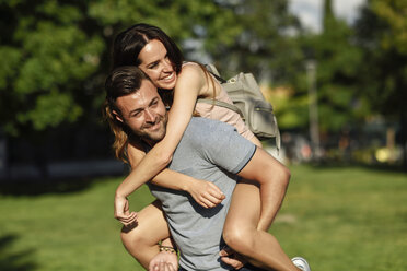 Happy man giving girlfriend a piggyback ride in park - JSMF00351