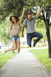 Carefree couple jumping in park - JSMF00354