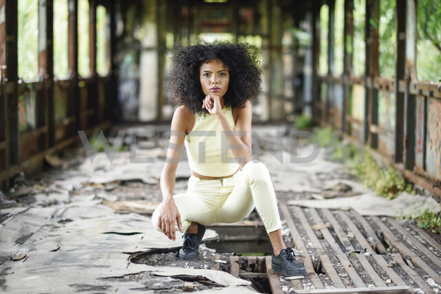 Portrait of fashionable young woman crouching in abandoned and destroyed old train - JSMF00372