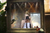 Mirror image of woman taking selfie with camera in bathroom - REAF00338
