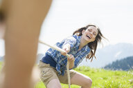 Cropped shot of mid adult couple playing tug of war, Wallberg, Tegernsee, Bavaria, Germany - CUF34715