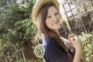 Portrait of teenage girl in straw hat in garden - CUF34724